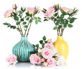 Beautiful pink and white roses in vases isolated on white — Stock Photo