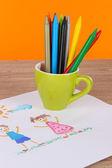 Lápices de colorido en la taza en la mesa sobre fondo naranja — Foto de Stock