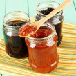 Tasty jam in banks on table — Stock Photo