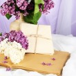 Composition with lilacs on light fabric background — Stock Photo #25707793
