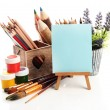 Pencils in wooden crate, paints, brushes and easel, isolated on white — Stock Photo #25707953