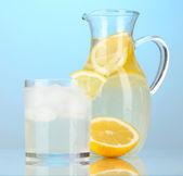 Lemonade in pitcher and glass on blue background — Stock Photo