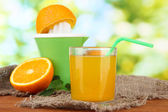 Citrus press, glass of juice and ripe oranges on brown wooden table — Stock Photo
