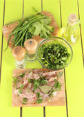 Chicken meat in glass plate,herbs and spices on wooden table — Fotografia Stock