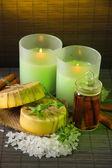 Fatto a mano sapone e candele su sfondo opaco di bambù — Foto Stock