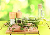 Chicken meat in glass plate,herbs and spices on nature background — Stock Photo