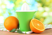 Citrus press and ripe oranges on brown wooden table — Stock Photo