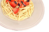 Spaghetti with tomatoes and basil leaves isolated on white — Stock Photo