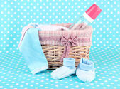 Beautiful basket of baby clothes on a blue background — Stock Photo