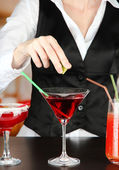 Barmen hand with shaker pouring cocktail into glass, on bright background — Stock Photo