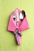 Cuillère fourchette et couteau en serviette sur fond de tissu quadrillé — Photo