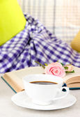 Composition with cup of drink, book and flowers on home interior background — Stock Photo
