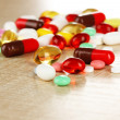 Assortment of pills, tablets and capsules on wooden table — Stock Photo