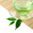 Transparent cup of green tea on bamboo mat, isolated on white — Stok fotoğraf