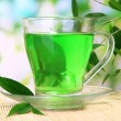 Transparent cup of green tea on bamboo mat, on nature background — Stok fotoğraf