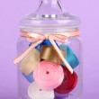 Stock Photo: Glass jar containing various colored ribbons on lilac background