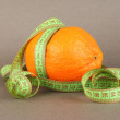 Stock Photo: Orange with measuring tape, on color background