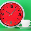 Cup coffee and clock on green background — Stock Photo