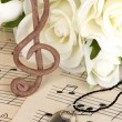 Treble clef, pendant and roses on musical background — Stock Photo