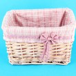 Stock Photo: Wicket basket with pink fabric and bow, on color background