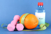 Orange with measuring tape, dumbbells and bottle of water, on color background — ストック写真