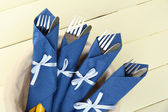 Forks and knives wrapped in blue paper napkins, on color wooden background — Stock Photo