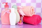 Dětské kosmetiky a ručníky v koupelně na fialové dlaždic stěna pozadí — Stock fotografie
