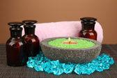 свеча в каменные чаши с морской солью, на бамбук циновка, коричневый фон — Стоковое фото