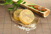 Hand-made soap and sea salt on grey bamboo mat — Stock Photo