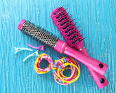 Scrunchies, hairbrush and hair - clip on a blue background — Stock Photo