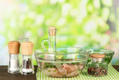 Chicken meat in glass bowl,herbs and spices on table on nature background — Stock Photo
