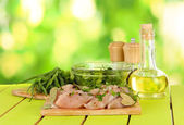 Chicken meat in glass plate,herbs and spices on table on nature background — Stock Photo