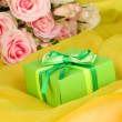 Beautiful gift on flowers background — Φωτογραφία Αρχείου