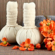 Herbal compress balls for spa treatment and towel on bamboo background — Stock Photo #25770295