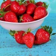 Strawberries in plate on blue background — Stock Photo #25772209