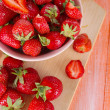 Strawberries in bowl on cutting board on wooden table — Stock Photo