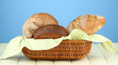 Bread in wicker basket, on wooden table, on color background — Стоковое фото