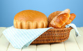 Composition with bread and rolls on wooden table, on color background — Stock Photo