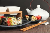 Tasty Maki sushi - Roll on green leaf on table on gray background — Stock Photo