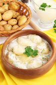 Tender young potatoes with sour cream and herbs in wooden bowl on tablecloth close-up — Stock Photo