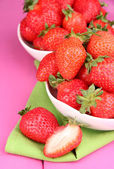 Fresh strawberry in bowl on pink wooden background — Stockfoto