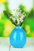 Beautiful mountain daffodils in color vase, on wooden table on bright background — Stock Photo