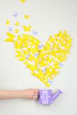 Papillon de papier jaune en forme de coeur mouche sur arrosoir — Photo