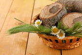Many spikelets and chamomile on satin in basket on wooden background — Stock Photo