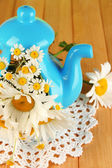 Beautiful bouquet chamomiles in teapot on wooden table close-up — Stock Photo