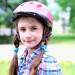 Portrait of little girl in helmet at  park — Stock Photo