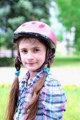 Portrait of little girl in helmet at park — Stock Photo