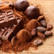 Composition of chocolate sweets, cocoa and spices on wooden background — Stock Photo