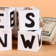 "Stock Photo: White paper cubes labeled ""News"" with money on beige background"