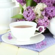 Composition with beautiful lilac flowers, tea service on wooden table, close up — Stock Photo